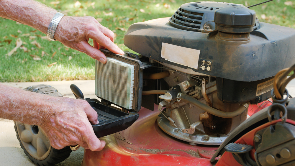 landscaper doing maintenance and replacing air filter on lawn mower